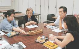 かつて貞山堀を航行した舟の模型を示しながら語る女性(左から2人目)の思い出話を聞く参加者