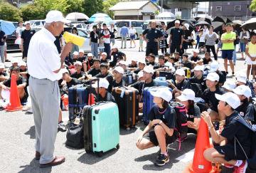 出発式で県体育協会の東島敏隆理事長(左)から激励を受ける県選手団=佐賀市の県総合運動場