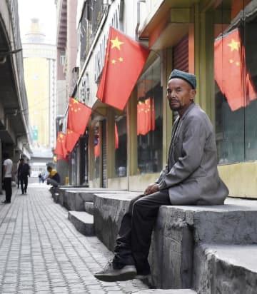中国の国旗が掲げられた通りに座る男性=7月、中国新疆ウイグル自治区ウルムチ(共同)
