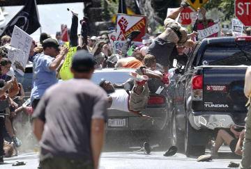2017年8月、米南部バージニア州シャーロッツビルで開かれた白人至上主義のグループの集会で、反対派が集まっていた付近に車が突っ込み、宙に舞う人々=(ライアン・M・ケリー/デーリー・プログレス提供、AP=共同)