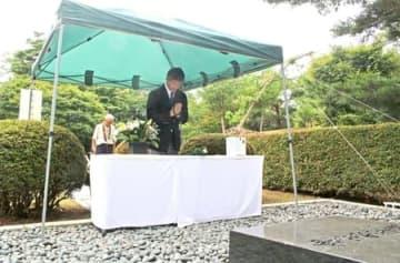 献花台の前で手を合わせる桜井雅浩市長=11日、柏崎市緑町