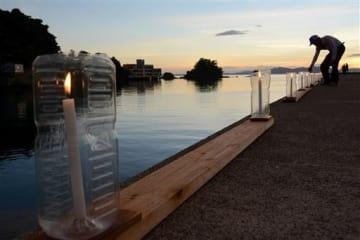 夕焼けに染まる八代海や旧赤崎小を背景に、波止場を彩る灯籠=津奈木町