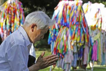 終戦の日を前に、千鳥ケ淵戦没者墓苑で手を合わせる男性=14日午後、東京都千代田区