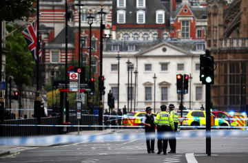 14日、ロンドンの英国会議事堂前に車が突っ込んだ後、規制された道に立つ警察官(ロイター=共同)