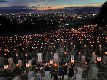 多くの提灯がともるなか、墓前で静かに手を合わせる人たち(14日午後7時15分、京都市東山区・大谷祖廟)