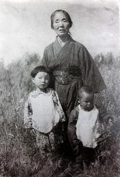 旧満州国の開拓地で撮影された幼き日の直美さん(左)、祖母、弟。妹の写真は残っていない=1942年