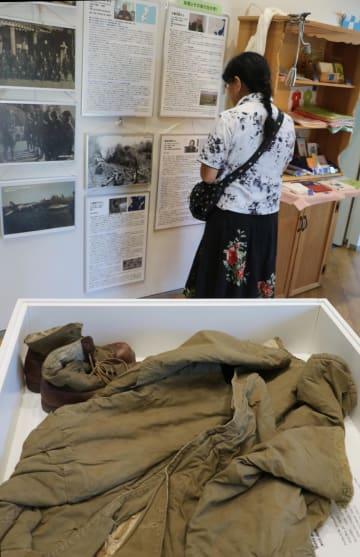戦争体験を紹介するパネルやシベリアから持ち帰った防寒着などを展示する報告展=ナガサキピースミュージアム