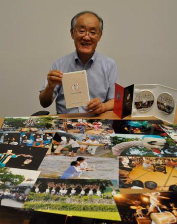 【DVD写真集「三重の祭唄」を紹介する北出さん(手前は収録写真の一部)=津市内で】