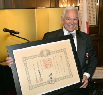 14日、米ニューヨークの日本総領事公邸で開かれた叙勲伝達式で、賞状を手に笑顔のボビー・バレンタインさん(共同)