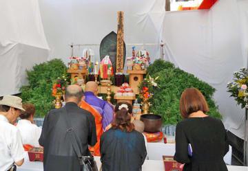 法要で慰霊碑に手を合わせる参列者ら=14日、大阪市城東区の京橋駅