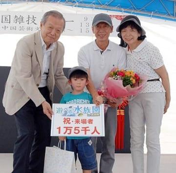 1万5千人目の来場者となった谷口碧羽ちゃん(左から2人目)=14日、湯梨浜町の中国庭園燕趙園
