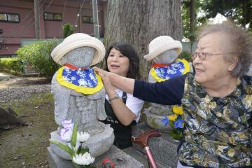 六地蔵に「べろ掛け」を付ける西村麗子さん(右)とえりさん
