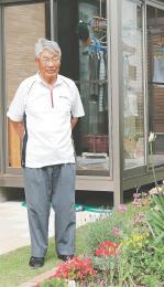 震災から4年9カ月後に再建した自宅の庭に立ち、花壇を眺める古沢さん