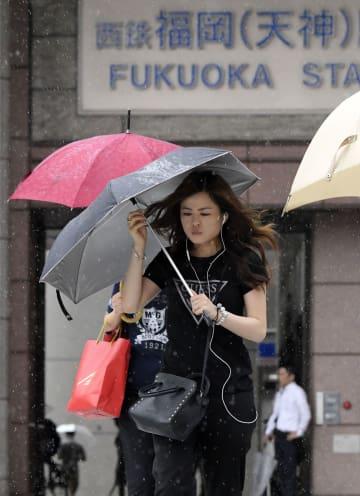 台風15号の影響で強まる風雨の中、傘を差して歩く女性=15日午前、福岡市