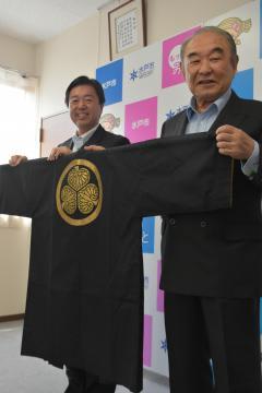 加藤浩一さん(右)からはんてんを受け取る高橋靖市長=水戸市中央