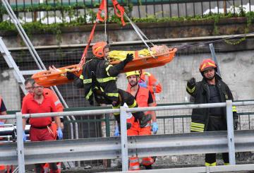 14日、イタリア北部ジェノバの高架橋崩落現場で、負傷者を運び出す救助隊員ら(AP=共同)