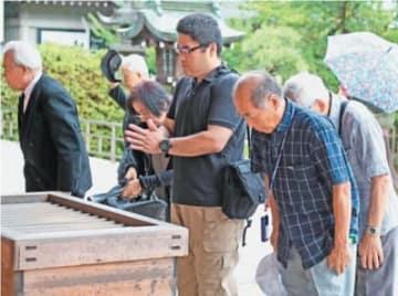 手を合わて戦没者の冥福を祈る遺族ら=15日午前11時27分、大分市の県靖国神社