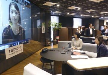 7月、テレワークを促す催しで、テレビ会議に参加する野田総務相(右下)=東京都内