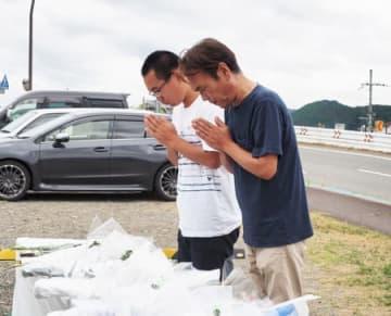 献花台で花を手向け、祈りをささげる余田捺希さん(左)と父の正徳さん=15日午前9時、福知山市上柳