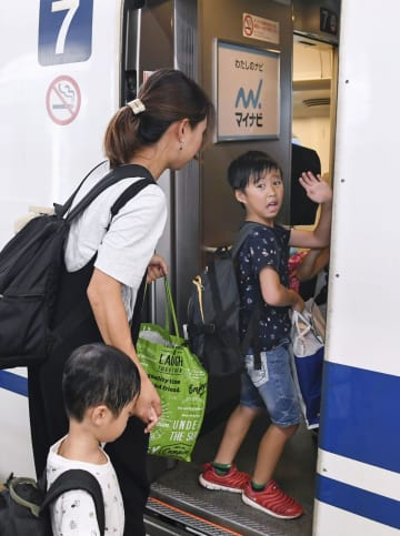 お盆のUターンラッシュがピークを迎えたJR新大阪駅で、新幹線のデッキから見送りの祖父母に手を振る男の子=15日午前