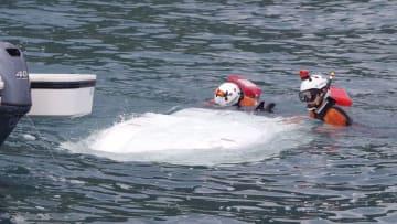 岩手県久慈市沖で見つかった、転覆したボートを調べる仙台航空基地の職員=15日午前(八戸海上保安部提供)