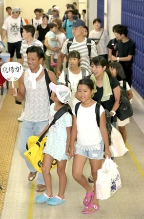 大きな荷物を持った家族連れらで混み合う佐渡汽船新潟港ターミナル=15日