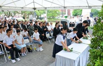 戦亡者慰霊祭で花を供える参列者=鹿児島市の探勝園