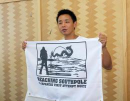 今回準備したオリジナルの旗を手に意気込みを語る阿部さん。南極点到達時には国旗と秋田県の旗と共に立てる