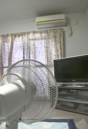 エアコンが壊れたままの室内。生活保護を受給する女性はカーテンを閉めて日差しを遮り、扇風機で過ごしている=8月7日、福井県福井市内