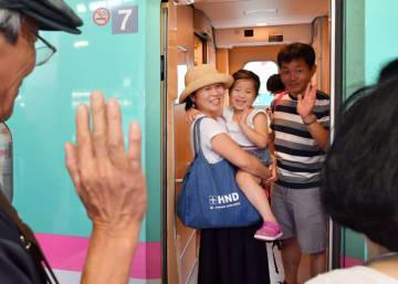 新幹線に乗り込み、見送る祖父母に「またね」と笑顔で手を振る親子=15日、盛岡市・JR盛岡駅