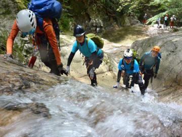 勢いよく水が流れる岩の斜面を登るクライマーたち(大津市葛川坊村町・白滝谷)