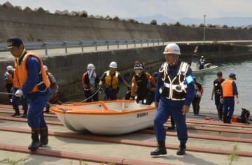 3人が乗っていたボートを引き揚げる八戸海上保安部関係者ら=15日午前11時55分ごろ、久慈市の久喜漁港