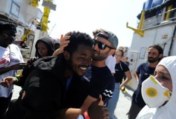15日、マルタの港に到着し、笑顔を見せる難民の男性(中央)(ロイター=共同)