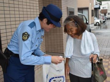 支店を訪れた女性(右)に啓発グッズを手渡す大浦署員=十八銀行新戸町支店