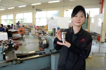 旋盤の前で、製作した鉄製の部品を持つ今村華蓮さん=八代市