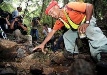 理稀ちゃんを発見した山中の沢で、状況を説明する発見者の尾畠さん(右端)。右手で示す石に座っていたという