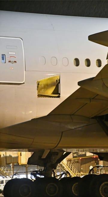 アメリカン航空61便ボーイング777の胴体。主翼の付け根付近にはパネルがなくなったと思われる痕跡が見える(中央)=16日夜、成田空港