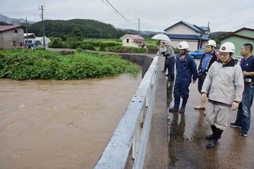 相内川の水位上昇を警戒する消防団員ら=16日午後3時53分、五所川原市太田