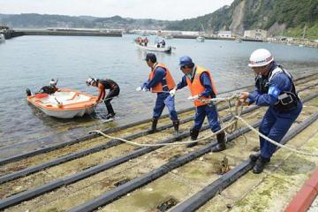 沖合で発見され海岸に引き上げられるボート=15日午前11時40分ごろ、岩手県久慈市・久喜漁港