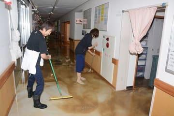 床上浸水したむつ市川内町の特別養護老人ホーム「せせらぎ荘」で、施設内の水をかき出す職員=17日午前8時10分ごろ