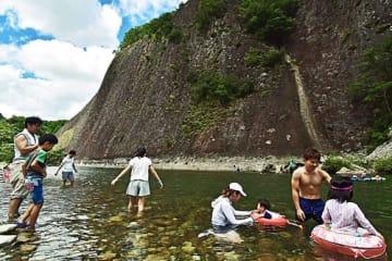 【国の天然記念物「古座川の一枚岩」の前で川遊びを楽しむ家族連れ(和歌山県古座川町相瀬で)】