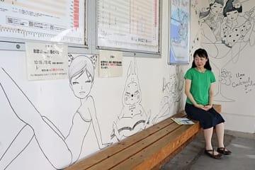 【ベンチに座っているように見える作品を描いた須川まきこさん(16日、和歌山県みなべ町芝で)】