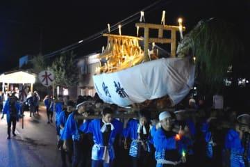 ろうそくの明かりをともした舟を担いで練り歩く住民ら