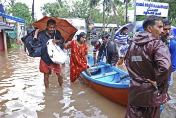 インド南部ケララ州で、洪水に見舞われ避難する人々=16日(AP=共同)
