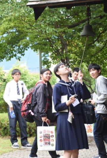 旧渋民尋常小学校に設置してある鐘を鳴らし、石川啄木に思いをはせる高校生=17日、盛岡市渋民