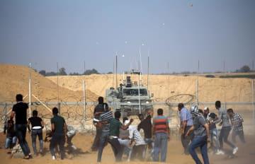 パレスチナ自治区ガザ南部で、イスラエル軍に投石するパレスチナの人々=17日(ロイター=共同)