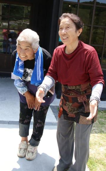 笑顔で案内所の来訪者を迎える綾香クニさん(左)と綾香和枝さん=平戸市春日町
