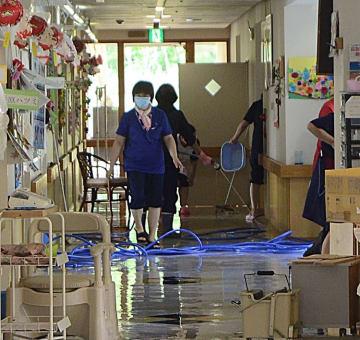 床上浸水した施設内の片付けに追われる職員=17日午前10時10分ごろ、むつ市川内町