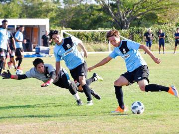 GK原田とDF竹田をかわしてゴールを狙うFW山岸(右)=県フットボールセンター