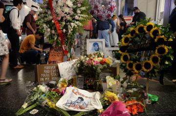 米ハリウッドで、アレサ・フランクリンさんの星形プレートの上に供えられた花束や写真=16日(共同)